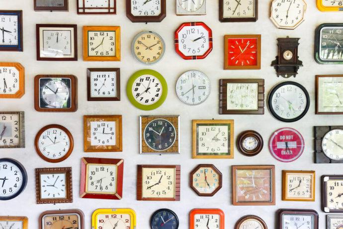 Vários relógios diferentes pendurados em uma parede.