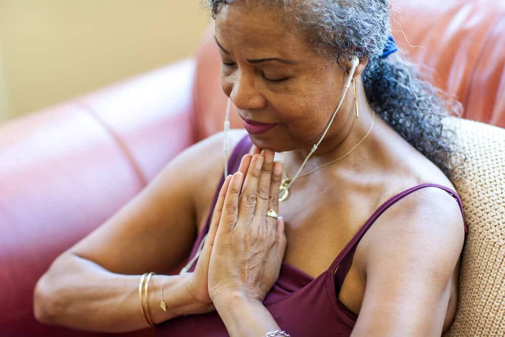 Mulher negra de meia idade meditando com as mãos próximas ao peito.